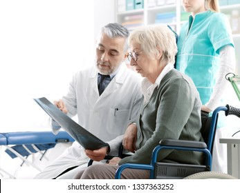 Professional radiologist examining an x-ray image with a senior patient during a visit at the clinic, the doctor is pointing and giving advices