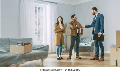 Professional Real Estate Agent Shows Bright New Apartment to Young Couple. Successful Young Couple Becoming Homeowners, Seal the Deal with Real Estate Broker by Handshake. Bright Home with Big Windows