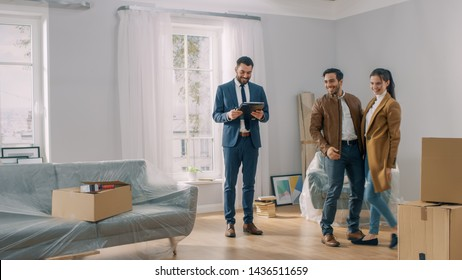 Professional Real Estate Agent Shows Bright New Apartment to a Young Couple. Successful Young Couple Ready to Become Homeowners. Spacious Bright Home with Big Windows.