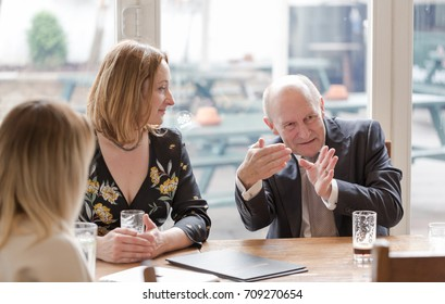 Professional real people, young adult woman, senior man, having informal business meeting in pub at glass of dark beer. Candid unposed horizontal shot.
