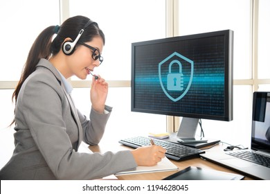 professional receptionist wearing earphone talking with customer and recording the problem to solve cyber security problem.