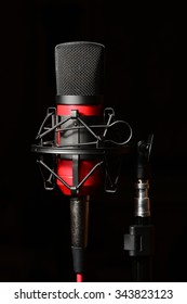 Professional recording studio condenser microphone attached to shock mount, isolated on black background