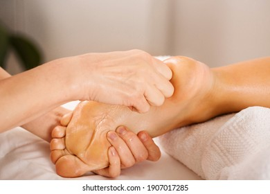 Professional relaxing massage for legs and feet. Energetic foot cleaning in a stream of Reiki, close-up