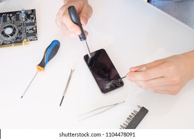 Professional repairman fixing dropped phone broken screen in service center