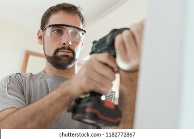 Professional repairman with protective goggles, he is using a drill and doing a home renovation