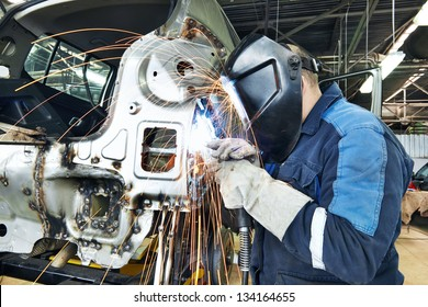 professional repairman worker in automotive industry welding metal body car with sparks