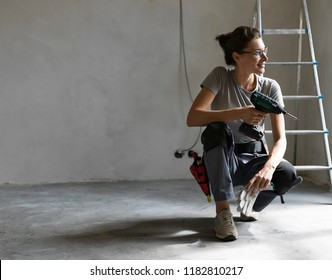 Professional repairwoman with tool belt doing a home renovation, she is posing and holding a drill