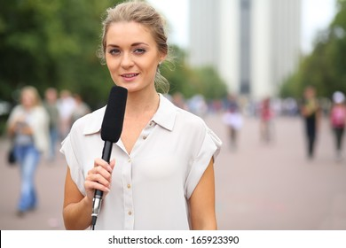 Professional reporter beautiful girl standing on the street with a microphone in hand