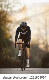 Professional road bicycle racer in action. Men cycling mountain road bike at sunset.