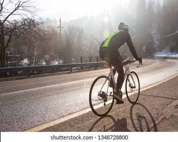 Professional road bicycle racer in action at dawn of the day