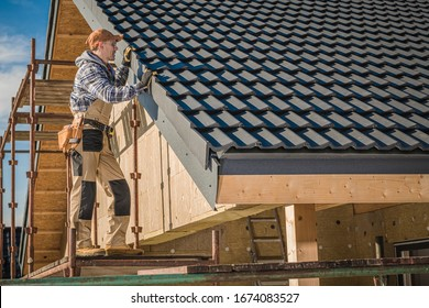 Professional Roofer Worker Finishing Ceramic Roof Tiles Installation. Smiling and Happy Worker on a Scaffolding.