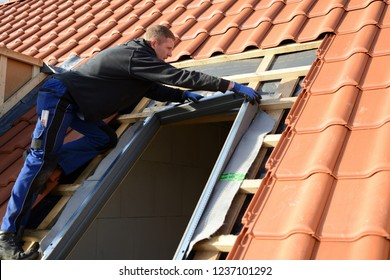 "professional roofing craftsman shows new work: window skylight model ""velux"" in roof with red tiles"