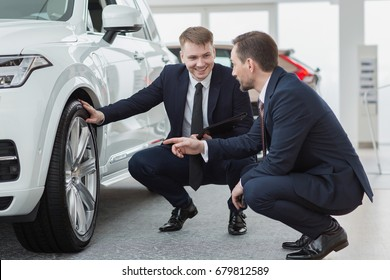 Professional salesman and his client mature businessman checking out wheels and tires of a new car at the dealership car dealer helping his customer man buying choosing automobile luxury driving