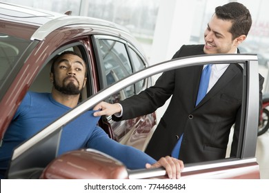 Professional salesman pulling out young African man out of the new car at the dealership client customer poverty kicking out forbidding annoying fighting argument profession occupation selling funny