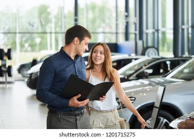 Professional salesman selling luxury car to beautiful female buyer at car dealership. Cauacasian young man holding black folder in hands, telling about car features to a young female driver.