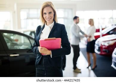 Professional saleswoman working at car dealership