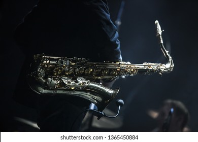 Professional saxophonist plays sax on concert stage in dark music hall.Classic musical instrument in close up.Shiny golden saxophone trumpet on jazz festival scene