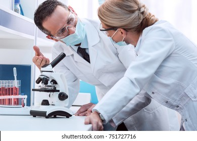 Professional scientists in white coats and sterile masks, using microscope and discussing work in laboratory