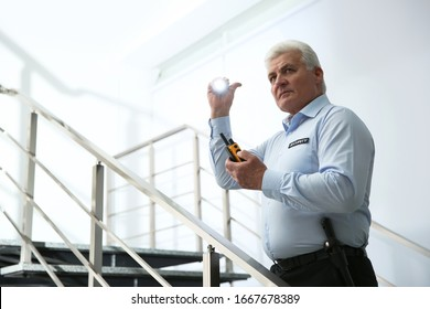 Professional security guard with portable radio set and flashlight on stairs indoors