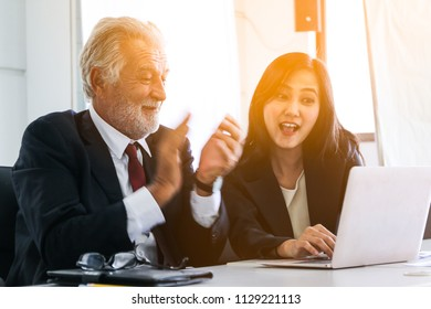 Professional senior businessman happy and clap  with his teaching or training for a lady trainee for data summarize report