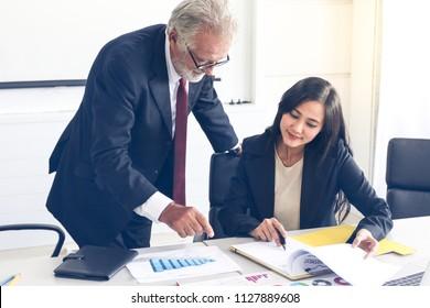 Professional senior businessman teaching or training a lady trainee for data summarize report