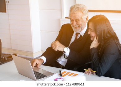 Professional senior businessman teaching or training a lady trainee for data summarize report