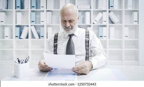 Professional senior businessman working in the office, he is checking paperwork and financial reports
