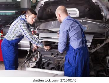Professional seroius adult mechanics repairing car of client