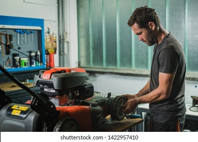 Professional serviceman is repairing a lawnmower, refitting a front wheel. Man repairing a mower in a workshop