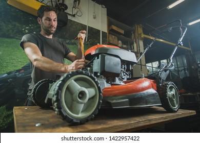 Professional serviceman is repairing a lawnmower, unscrewing a spark plug. Man repairing a mower in a workshop