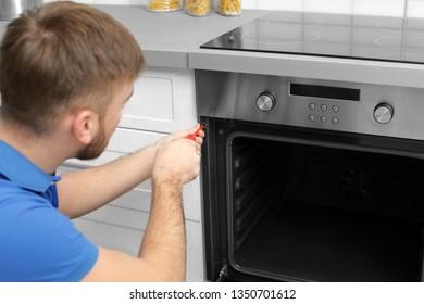 Professional serviceman repairing modern oven in kitchen