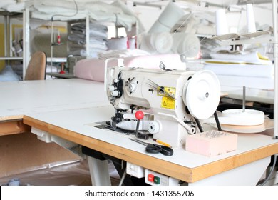 Professional sewing machine overlock in the workshop. Equipment for edging, hemming or stitching clothes in a tailor shop.