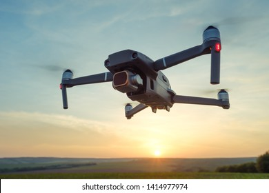 Professional shooting drone flies in the air at low altitude against a blue sky and orange sunset on an agricultural field with wheat. Sun disc. Drone makes photos. Modern new technology.