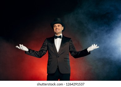 Professional showman wearing suit gloves and top hat standing isolated on blue and red background hands aside starting performance smiling happy