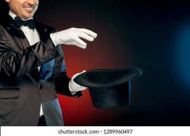 Professional showman wearing suit and gloves standing isolated on black and red background holding top hat making tricks close-up smiling cheerful