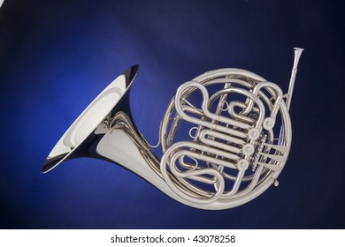 A professional silver French horn isolated against a spotlight blue background.