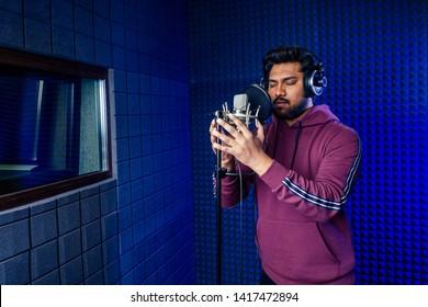 professional singing indian men headphones sound modern studio violet background recording song.