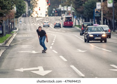 Professional skateboarder riding a skateboard slope on the capital city streets, through cars and urban traffic