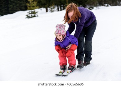 Professional ski instructor is teaching a child to ski on a sunny day on  a mountain slope resort with sun and snow. Family and children active vacation.