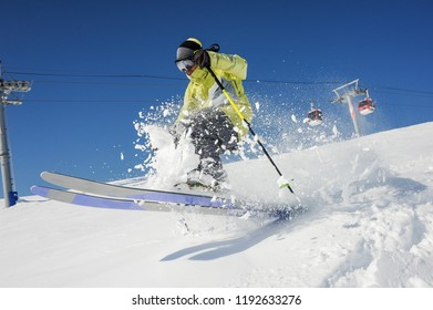 Professional skier dressed in bright yellow sportswear riding down the mountain slope in Georgia, Gudauri on sunny day