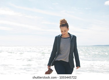 Professional smart young woman carrying shoes walking on beach smiling with sunny sea and sky background, outdoors. Healthy curvy female having break in coastal nature, recreation leisure lifestyle.