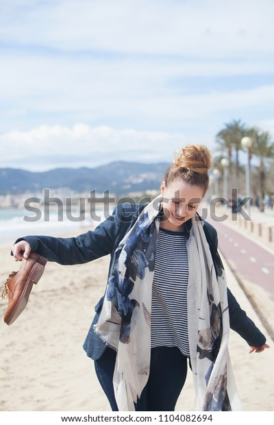 Professional smart young woman carrying shoes walking on beach smiling with sunny sea and sky in background, outdoors. Healthy female, enjoying coastal break, recreation leisure lifestyle.