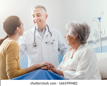 Professional smiling doctor meeting a senior patient and her daughter at the hospital, medical service concept
