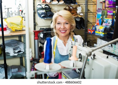 Professional smiling elderly tailor female working on sewing machine at studio