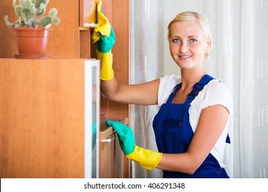 Professional smiling female cleaner doing regular clean-up in livingroom
