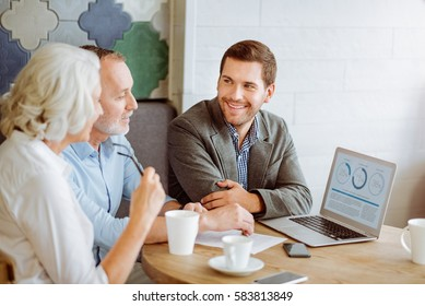 Professional smiling insurance manager talking with aged couple