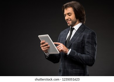 professional smiling young businessman using digital tablet isolated on black