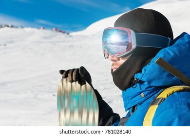 A professional snowboarder stands with his snowboard. Close-up. Portrait of a freerider