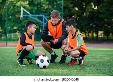 Professioneller Fußballtrainer erzählt seinen aufmerksamen Teenagern im Stadion während des Trainings die Strategie des Fußballspiels.