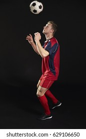 Professional Soccer Player Heading Ball In Studio